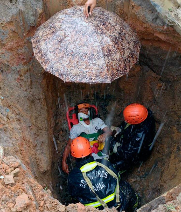Chovia no momento do resgate e bombeiros usaram um guarda-chuva para proteger a vítima - Foto: Divulgação | Corpo de Bombeiros