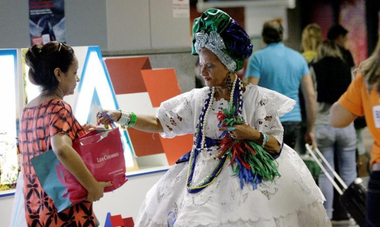 Baiana recepciona uma turista que chegou em Salvador - Foto: Raul Spinassé | Ag. A TARDE