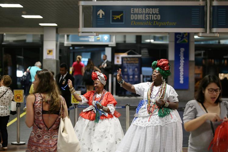 Baianas tipicamente trajadas distribuíam fitas do Senhor do Bonfim para os visitantes que deixavam a capital - Foto: Raul Spinassé l Ag. A TARDE
