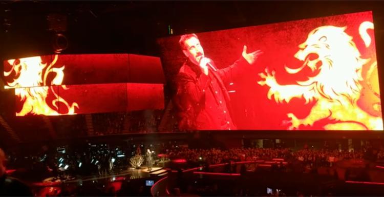 Enquanto a música era apresentada, um telão mostrava diversas cenas da série - Foto: Reprodução   YouTube