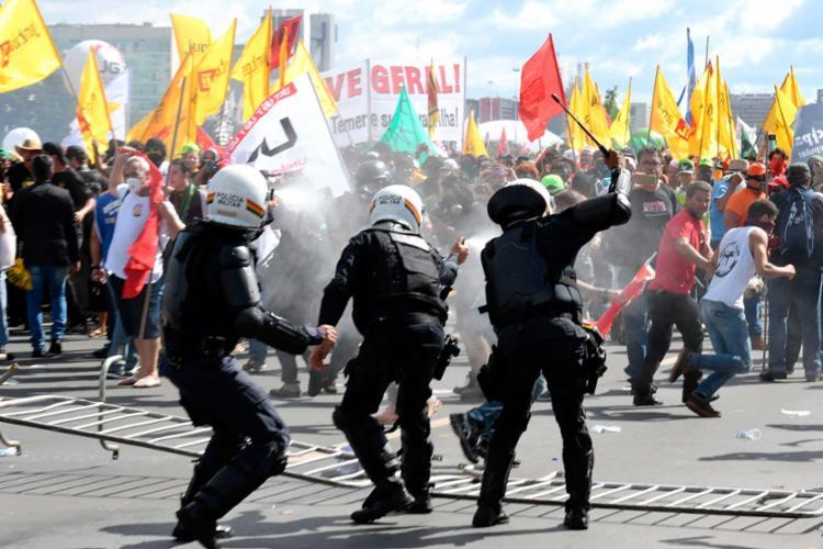 Em reação, os policiais têm que usar até cassetetes. - Foto: Andressa Anholete   AFP