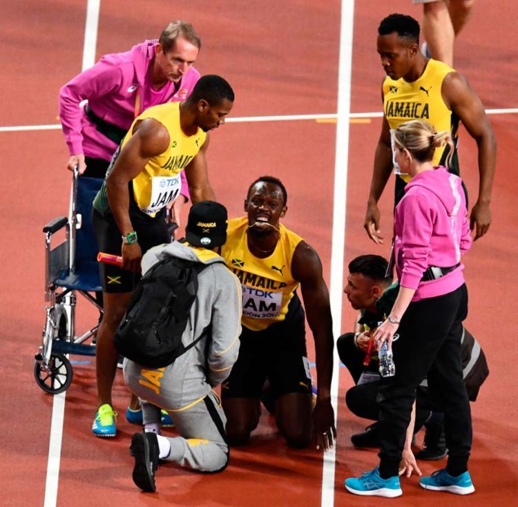 Bolt contorceu em dores e viu os adversários o ultrapassarem - Foto: AFP