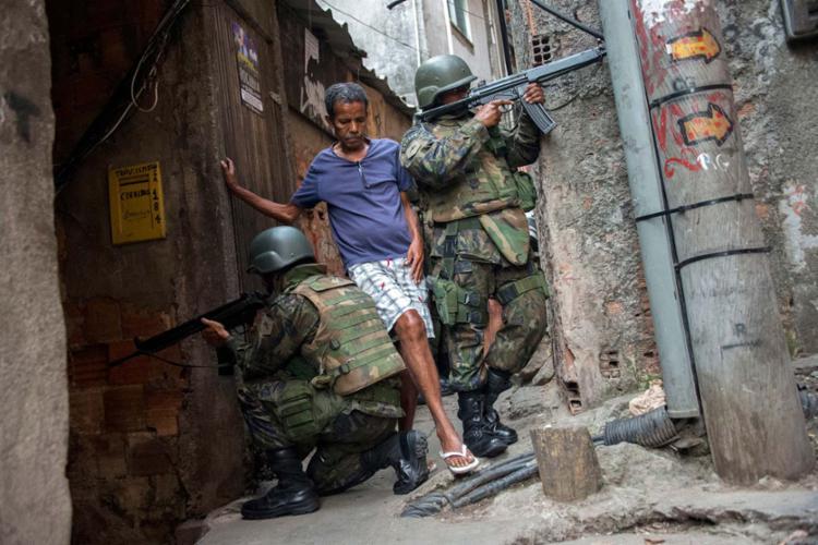 Moradores passam entre os militares do Exército na Rocinha - Foto: Mauro Pimentel | AFP