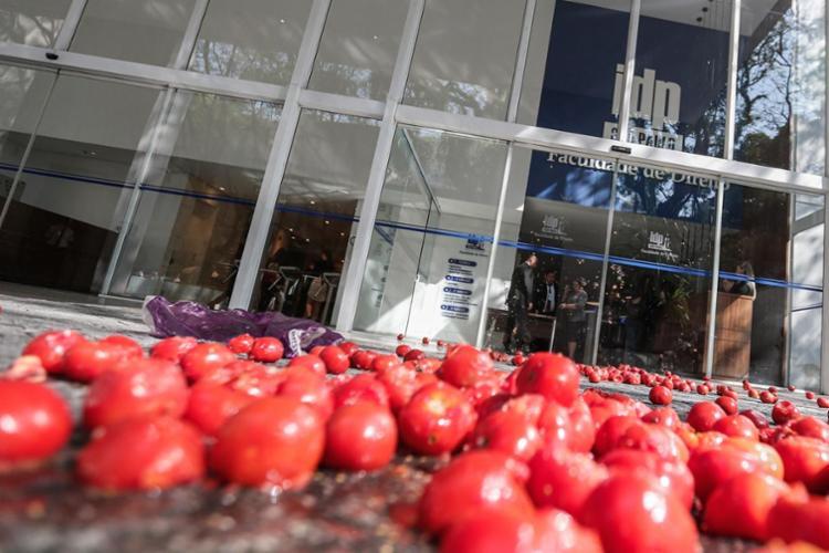 Os manifestantes jogam tomates sobre a calçada, a pista e contra carros de participantes que chegam ao evento - Foto: Suamy Beydoun/Agif | Estadão Conteúdo