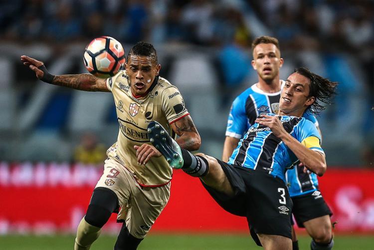 Álves (E), autor do gol dos equatorianos, disputa bola com gremista Geromel - Foto: Jefferson Bernardes l AFP
