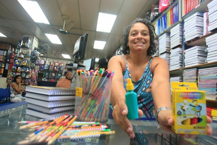 Vendedora Elaine Alves mostra a caixa de cola que deve ser vendida completa - Foto: Mila Cordeiro | Ag. A TARDE