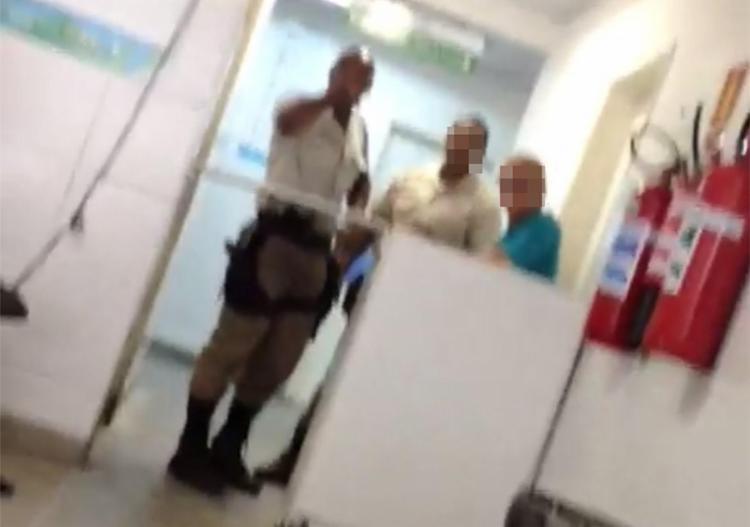 Na imagem retirada do vídeo, PM aparece em um balcão ao lado de dois homens - Foto: Reprodução