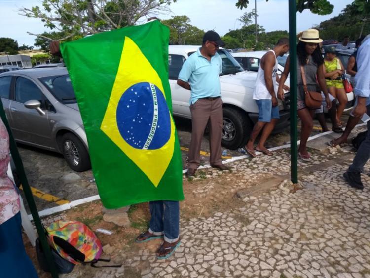 O ajudante de pintor, Wellington Silva, levou uma bandeira do Brasil em protesto contra a fila - Foto: Francisco Artur | Ag. A TARDE
