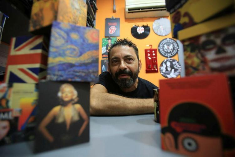 Jorge Itaitu, da Cinerama, vende camisetas e objetos com estampas de artistas, filmes e séries de TV. - Foto: Raul Spinassé | Ag. A TARDE