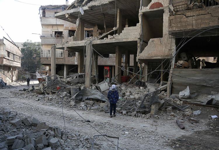 Menina síria olha para escombros de um hospital que foi destruído nesta quarta - Foto: Abdulmonan Eassa l AFP Photo
