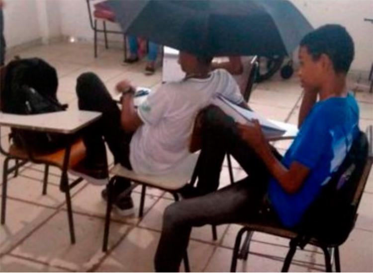 Estudante utilizou guarda-chuva para se proteger do vazamento de água no telhado - Foto: Reprodução   Radar 64