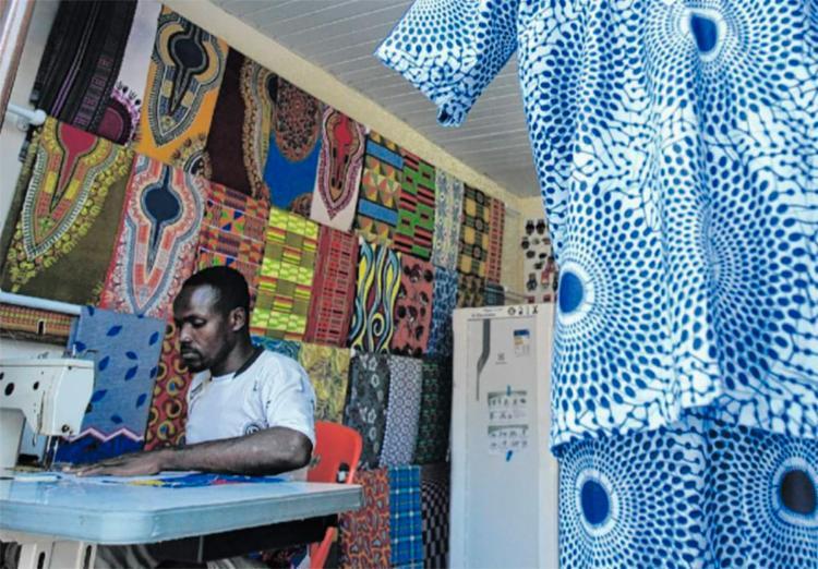 Refugiado há dois anos, Zakari começou vendendo as roupas que confecciona na rua - Foto: Alessandra Lori | Ag. A TARDE