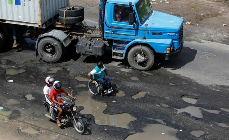 Entre buracos, cadeirante divide espaço com veículos - Foto: Raul Spinassé   Ag. A TARDE