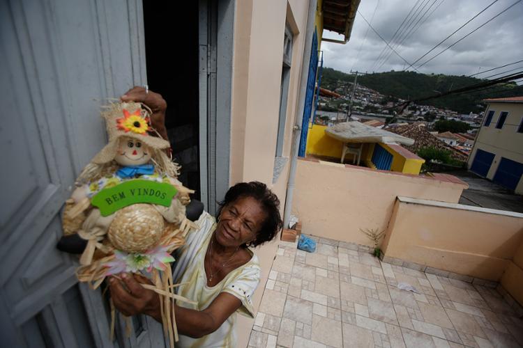 Dona Naná prepara a casa para o aluguel temporário e espalha cartazes de divulgação