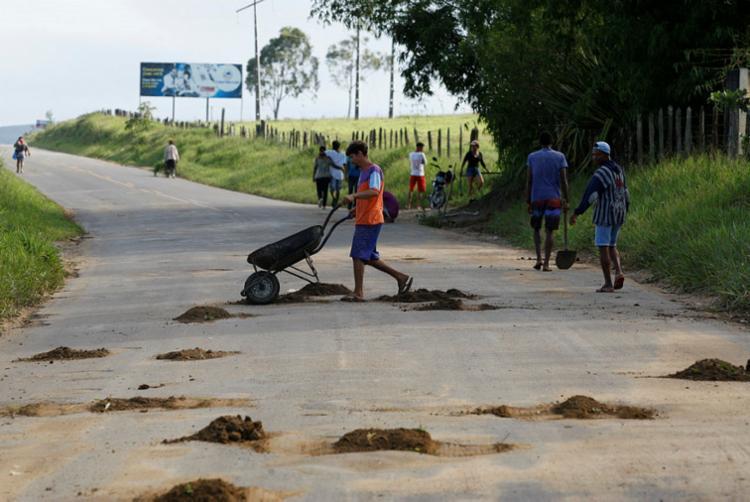 """Próximo à entrada de Amargosa, desempregados fazem """"bico"""" para ganhar uns trocados em trecho da esburacada BA-026 - Foto: Luciano da Matta   Ag. A TARDE"""