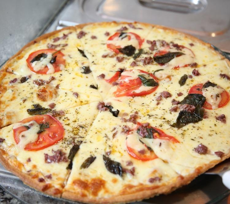 A pizza tem massa integral e recheio clássico: queijo, tomate e manjericão. Foto: Joá Souza / Ag. A TARDE