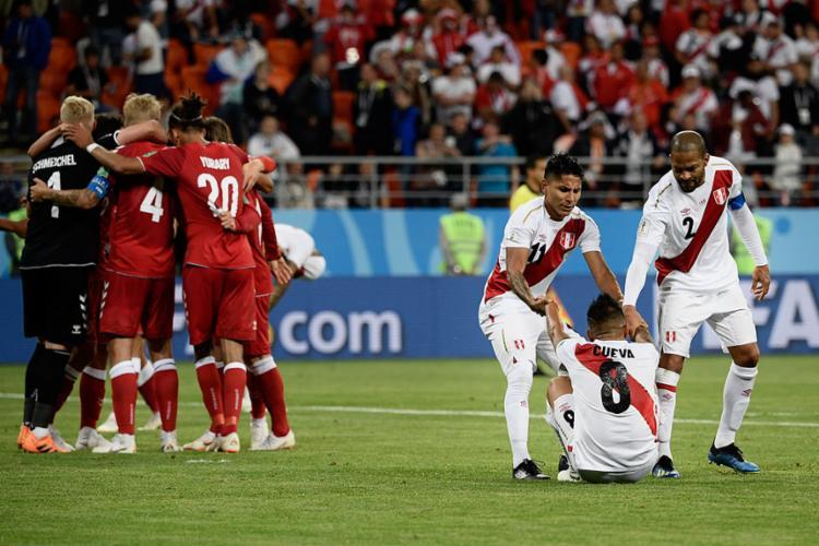 Jogadores da Dinamarca comemoram enquanto time do Peru lamenta a derrota - Foto: Filippo Monteforte | AFP
