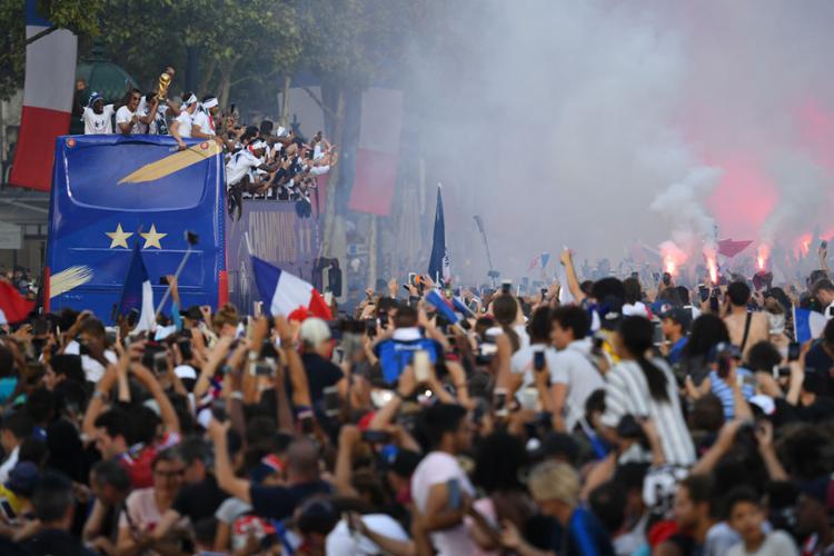 Em cima do ônibus aberto, os campeões mundiais faziam a festa com os torcedores - Foto: Jacques Demarthon | AFP