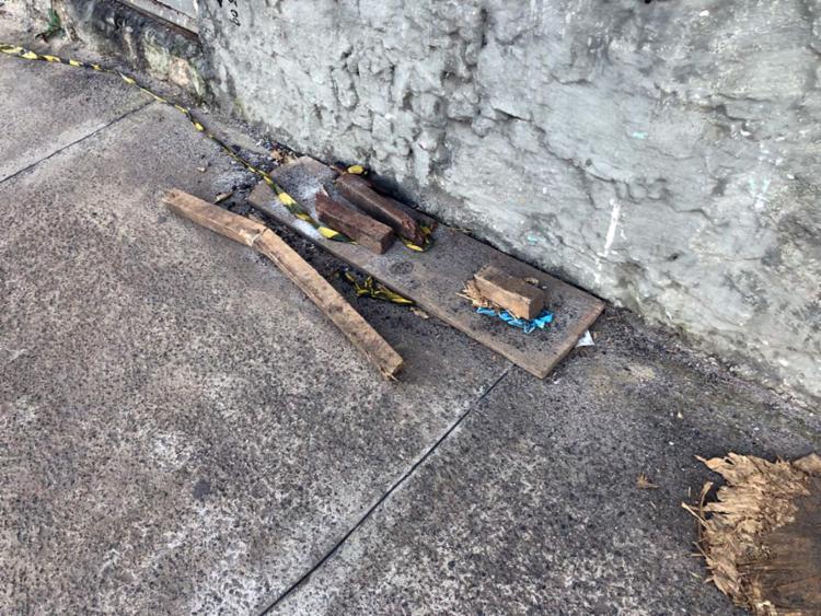 Pedaços de madeiras estão jogados na frente do edifício