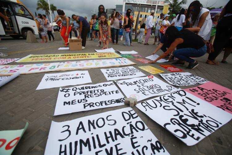 Docentes carregam cartazes na praça da igreja de Itapuã