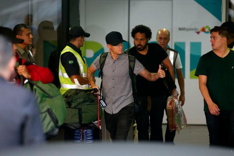 Philippe Coutinho acena para os torcedores após desembarque no aeroporto do Rio