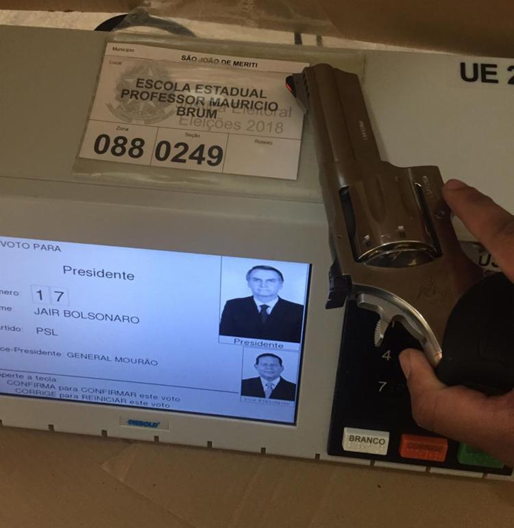 Uma arma aparece em cima de uma urna na Escola Estadual Professor Mauricio Brum, em São João do Mereti, interior do Rio - Foto: Cidadão Repórter via Whatsapp