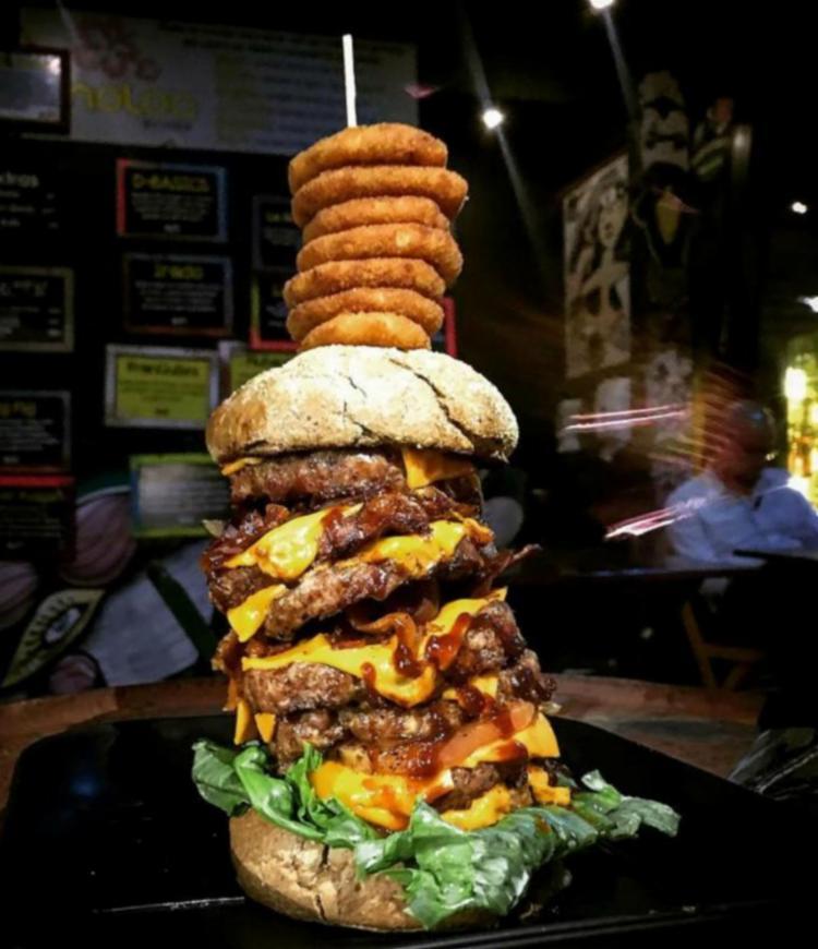 O hambúrguer é composto por sete carnes de 100g, fatias de queijo cheddar, cebola caramelizada e bacon, além do acompanhamento de sete anéis de cebola - Foto: Divulgação | Redes Sociais