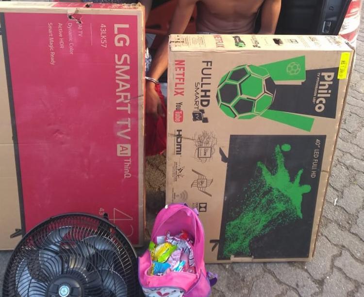 Com os suspeitos foram apreendidos dois televisores, uma LG 43 polegadas e uma Philco 40 polegadas, um ventilador e uma mochila com chocolates