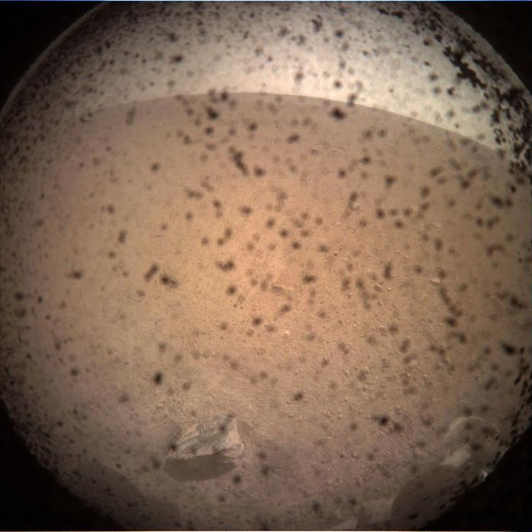 Primeira imagem enviada pela InSight após o pouso em Marte, ainda com a capota protetora sobre a lente da câmera - Foto: Nasa l AFP
