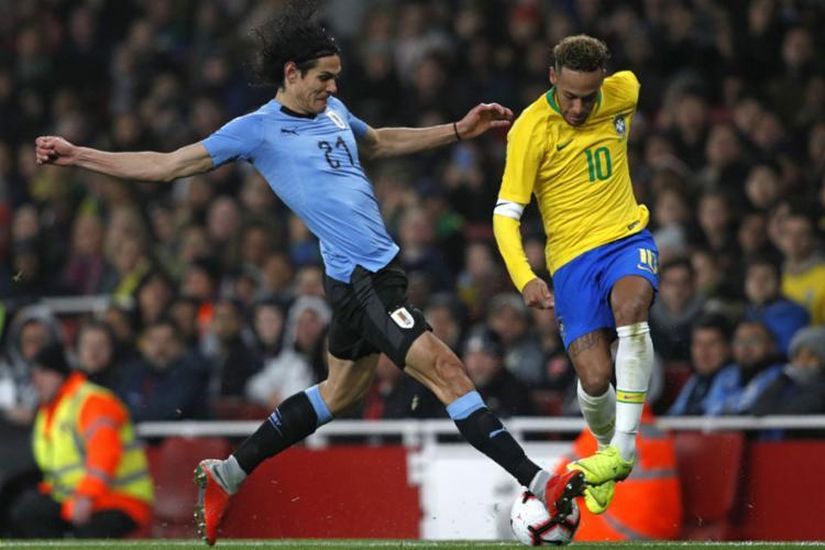 Neymar e Cavani disputam a bola durante amistoso em Londres - Foto: Adrian Dennis l AFP