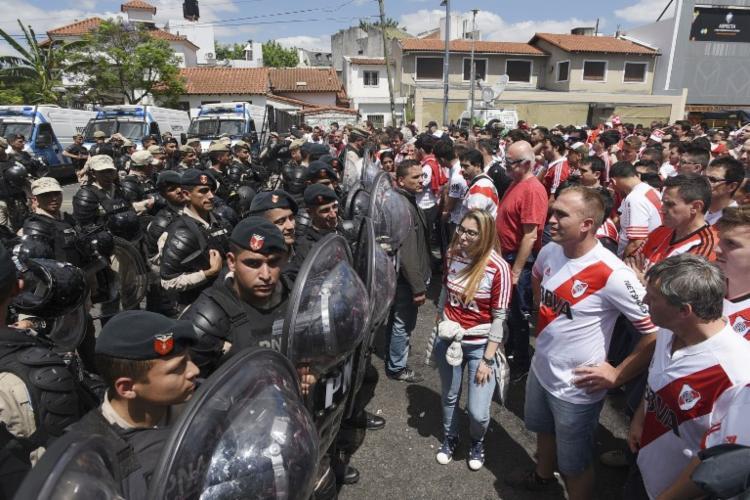 Policiais bloqueiam torcedores do River Plate no entorno do estádio Monumental após um ataque - Foto: Santiago Viana   AFP