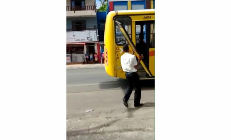 Em um vídeo circulado pelas redes sociais, gravado por um internauta, mostra o motorista recolhendo a porta que havia caído - Foto: Reprodução