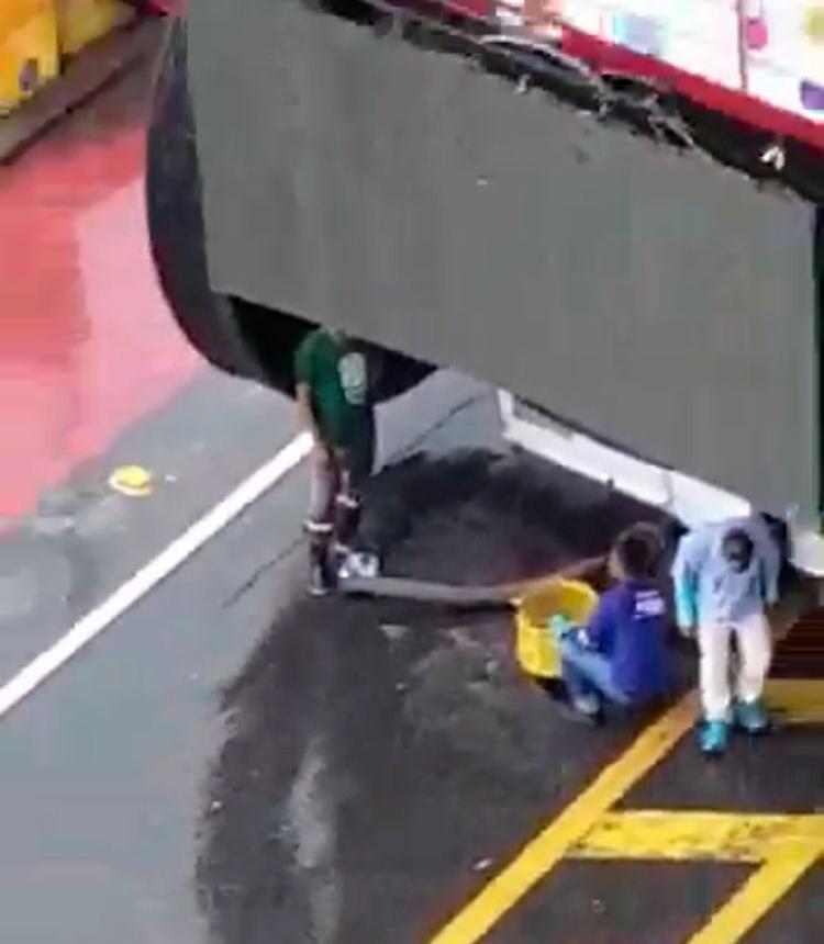 Caminhão e homens abrindo uma caixa de esgoto