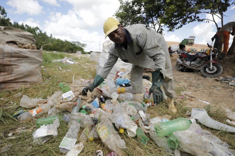 O catador Adilton Pereira revira o lixo em busca de recicláveis no aterro sanitário da cidade