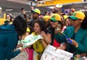 Atletas da seleção são recebidas com festa na chegada ao Brasil: