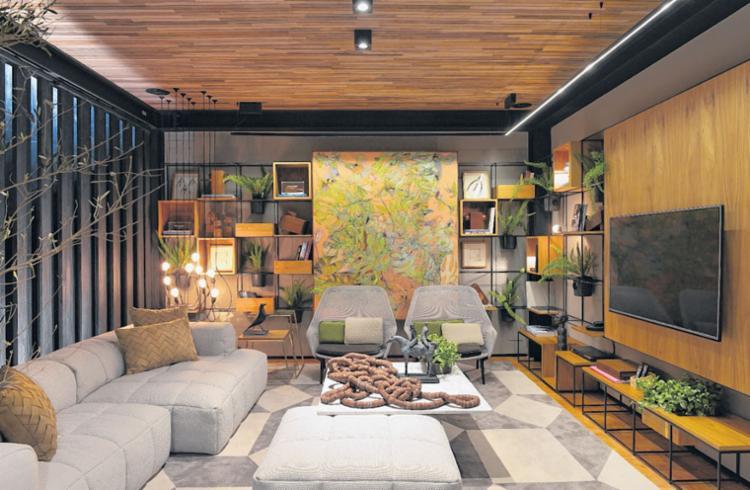 Laís Galvão optou por destacar uma obra de arte de grande formato no meio da estante com outros objetos, como livros e plantas - Foto: Marcelo Negromonte | Divulgação