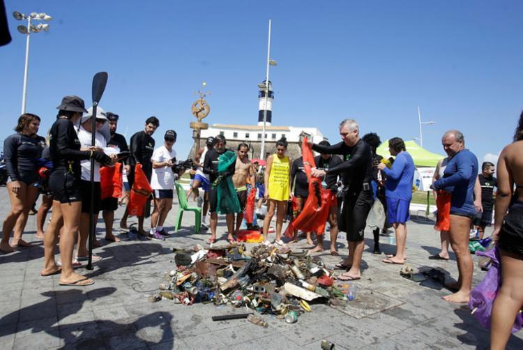 Mergulhadores exibem objetos tirados do mar