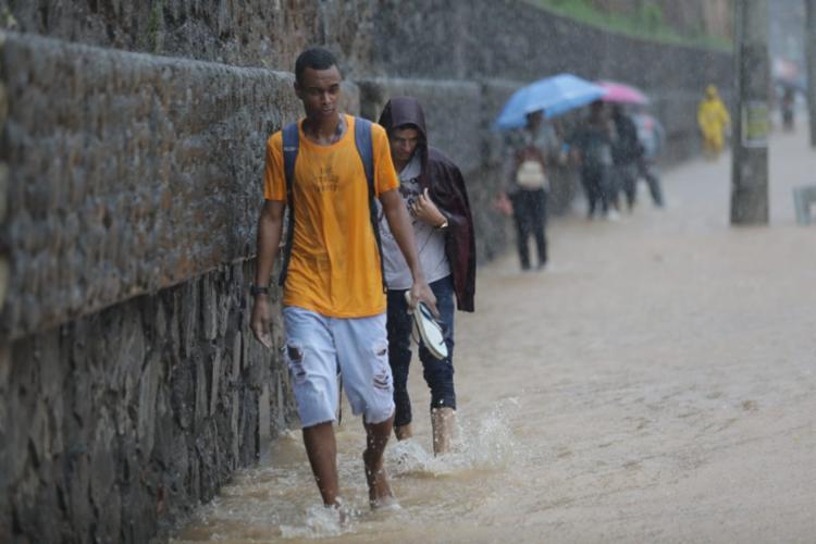 Luís Vitor atravessou a via alagada para ir ao trabalho   Foto: Raul Spinassé   Ag. A TARDE - Foto: Raul Spinassé   Ag. A TARDE