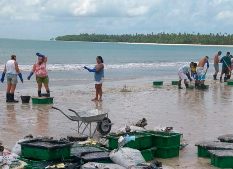 Voluntários auxiliam na remoção das placas de óleo na praia   Foto: Reprodução   Cidadão Repórter - Foto: Reprodução   Cidadão Repórter
