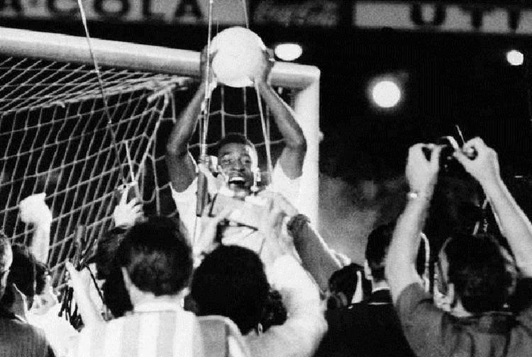 Pelé ergueu a bola ao cair nos braços da multidão que comemorava o milésimo gol   Foto: Divulgação - Foto: Divulgação
