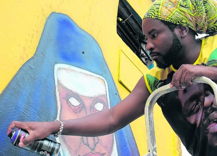 Lee grafita a santa baiana, na Rua E, em Castelo Branco | Foto: Filipe Augusto | Divulgação