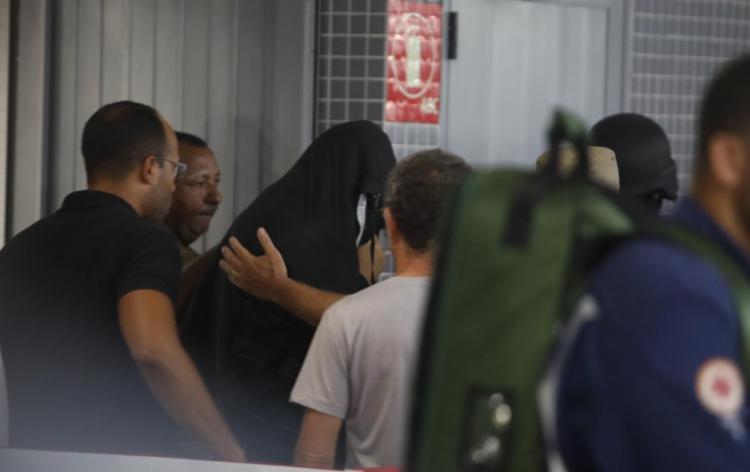 Homem que manteve refém saiu da Estação Acesso Norte com uma manta preta e acompanhado pela polícia | Foto: Felipe Iruatã | Ag. A TARDE