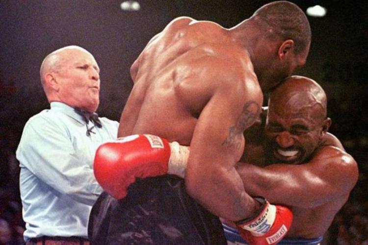 Momento exato em que árbitro Lane Mills percebe a mordida de Tyson em Holyfield | Foto: Jeff Haynes | AFP