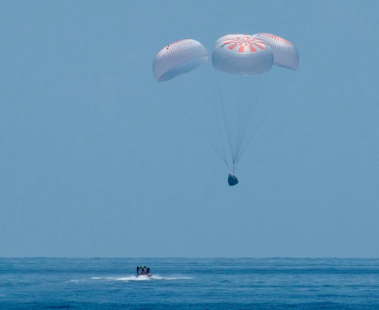 Os quatro paraquedas principais da cápsula Crew Dragon abriram e ficaram flutuando suavemente depois que a nave pousou no mar na costa de Pensacola | Foto: Bill Ingalls | AFP - Foto: Bill Ingalls | AFP