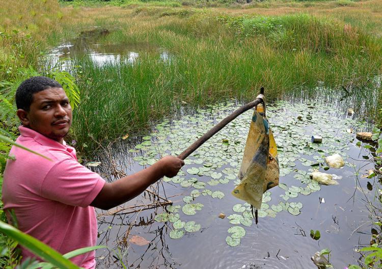 Morador da região, Leonis Alves mostra lixo em uma das nascentes da lagoa