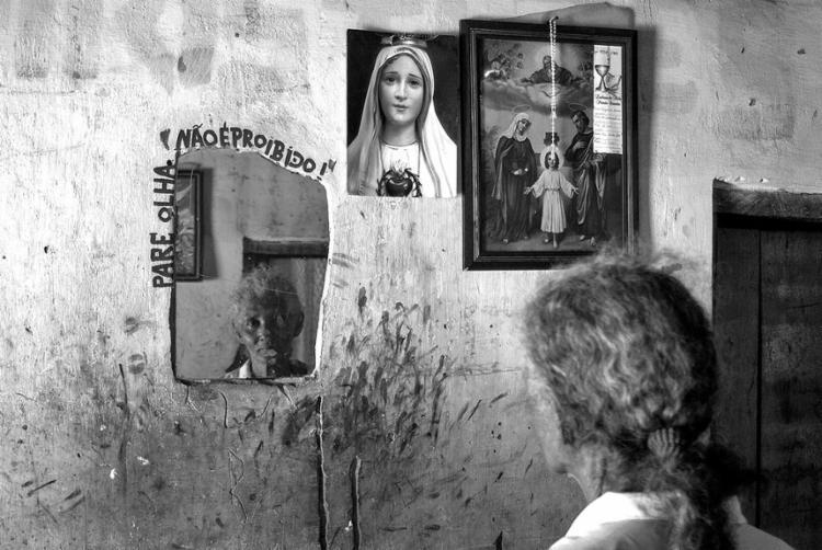 A senhora quilombola se olha no espelho mas não enxerga suas raízes. Em casa, imagens católicas que agora são combatidas pelos evangélicos da região | Foto: Alvaro Villela | Divulgação - Foto: Alvaro Villela | Divulgação