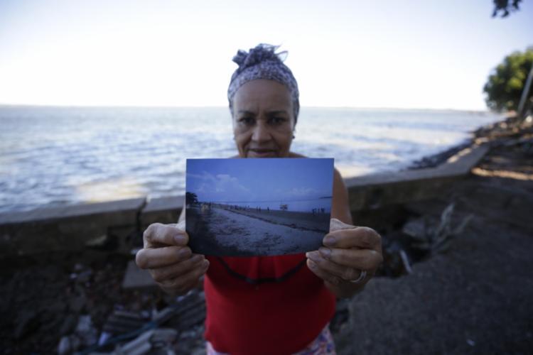 Moradora mostra foto de como era a praia de Cacha Pregos
