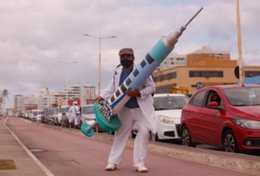 'Dr. Vacina': com seringa gigante, artista leva doses de alegria para filas de vacinação | Olga Leiria / Ag. A TARDE
